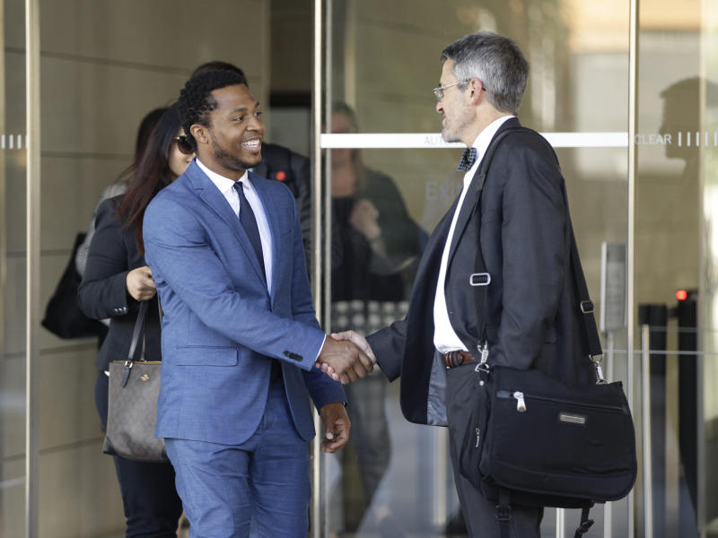 """Rapper Marcus Gray, left, shakes hands with his attorney, Michael A. Kahn, right, as they leave the federal courthouse downtown Los Angeles Thursday, Aug. 1, 2019. A jury has decided that Katy Perry, her collaborators and her record label must pay more than $2.78 million because the pop star's 2013 hit """"Dark Horse"""" copied a Christian rap song. It was an underdog victory for relatively obscure artist Gray, whose 5-year-old lawsuit survived constant court challenges. (AP Photo/Damian Dovarganes)"""