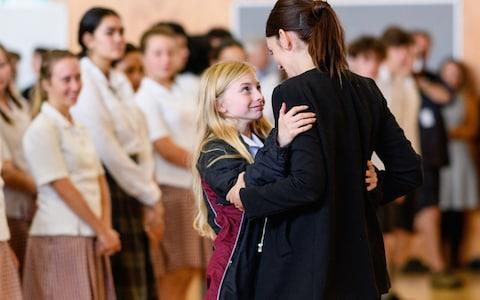 New Zealand Prime Minister Jacinda Ardern receives a hug from a student during her visit to Cashmere High School which lost two students during a mass shooting