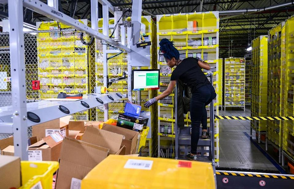 """In Staten Island, on top of tech-vest wearers, there are """"stowers,"""" """"pickers"""" and """"packers"""" who respectively load up products, match up products meant for the same customers and build shipping boxes (AFP Photo/Johannes EISELE)"""