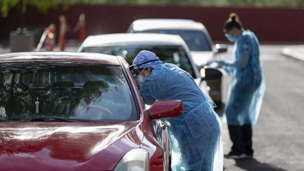 PHOTO: Healthcare workers wearing personal protective equipment (PPE) administer tests at an El Rio Health Covid-19 drive-thru testing site in Tucson, Ariz., July 13, 2020.  (Cheney Orr/Bloomberg via Getty Images)