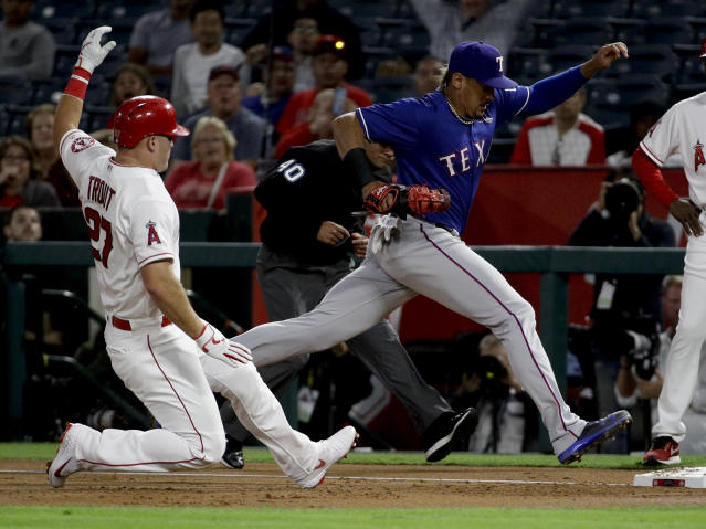 Texas Rangers first baseman Ronald Guzman, right, doubles off Los Angeles Angels' Mike Trout out at first after Shohei Ohtani lined out to Guzman during the first inning of a baseball game in Anaheim, Calif., Tuesday, Sept. 25, 2018. (AP Photo/Chris Carlson)
