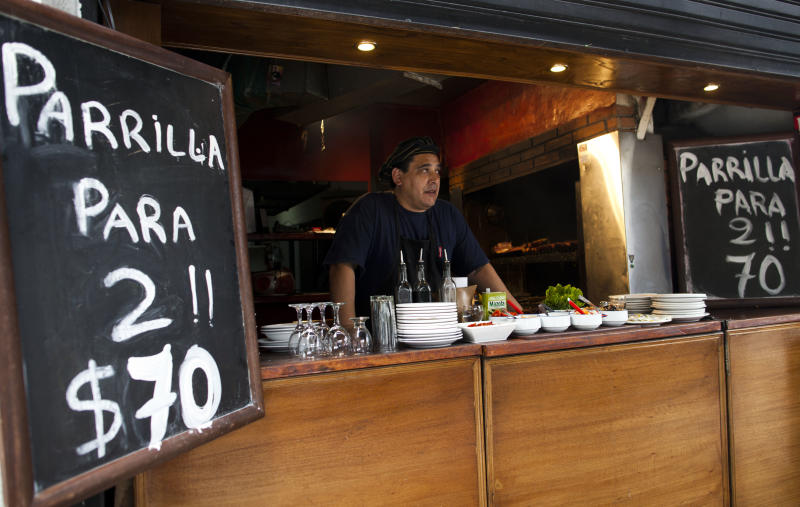 Pepe Gonzalez works at a restaurant offering barbecue for two people for 70 pesos in Buenos Aires, Argentina, Thursday, Jan. 17, 2013. The nation's currency's official rate is 4.96 pesos per US dollar, and the black market rate is about 7.50 pesos per US dollar. Close government allies have given up defending the official statistics service, known as INDEC, which announced Monday that Argentina's annual inflation was just 10.8 percent in 2012. Private economists have estimated that Argentina's inflation was actually 26 percent or more, making it the worst in all of Latin America. (AP Photo/Natacha Pisarenko)