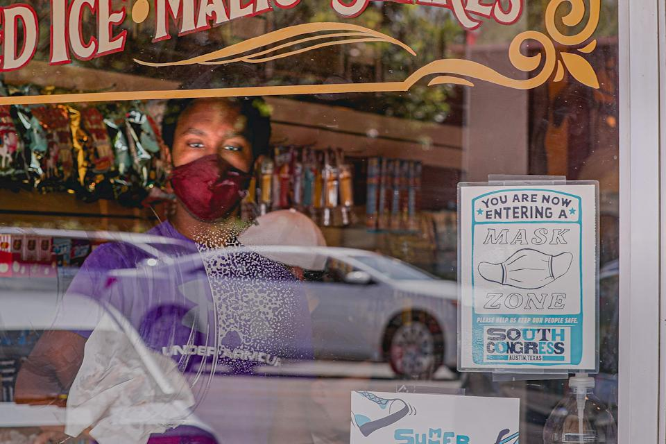 A store employee wearing a mask cleans a window with a sign requesting customers put on masks at a shop on South Congress Avenue. Travis County in Texas moved back to Stage 4 of COVID rules and health officials are asking residents who have yet to receive a coronavirus vaccine to sign up for one immediately.