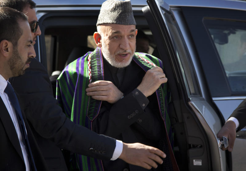 A Wednesday, March 6, 2013 photo shows Afghan President Hamid Karzai surrounded by his security as he arrives to the Afghan Parliament where he made a speech angering the United States with a promise to release prisoners currently at the U.S. controlled Bagram prison north of Kabul. Karzai has made several statements including accusing the U.S. of colluding with the Taliban, driving relations between the two countries to an all time low. (AP Photo/Anja Niedringhaus)