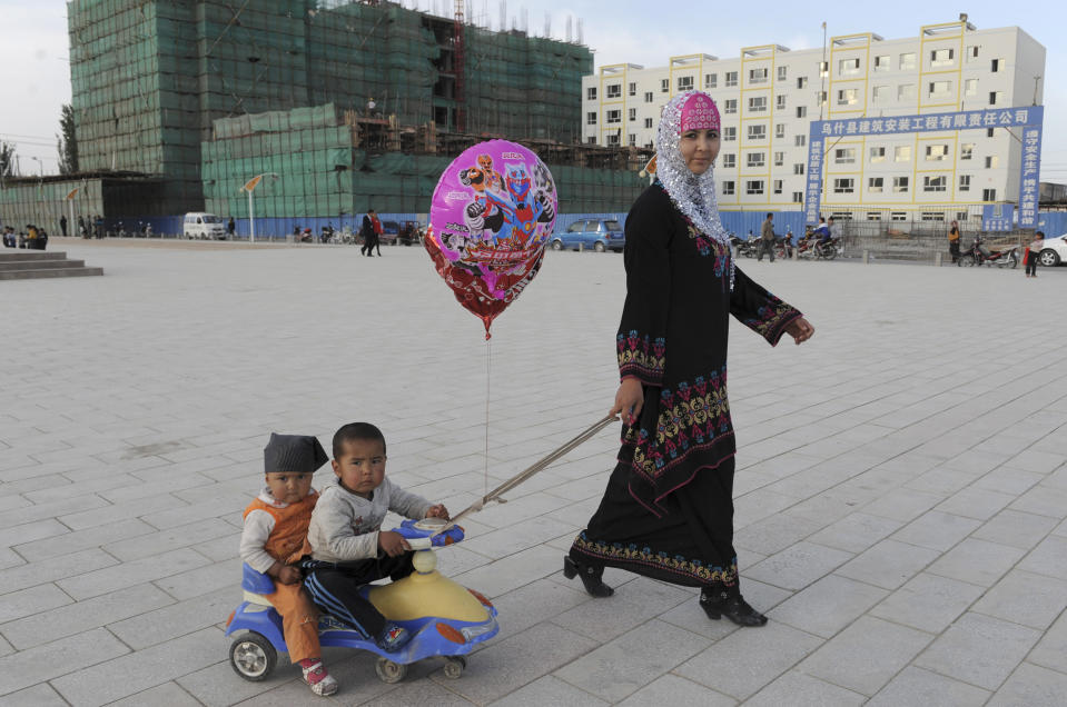 A Uighur woman pulls a buggy carrying her sons as she walks past residential buildings under construction in Uqturpan county, Xinjiang Uighur Autonomous Region May 3, 2012. Picture taken May 3, 2012. REUTERS/Stringer (CHINA - Tags: SOCIETY) CHINA OUT. NO COMMERCIAL OR EDITORIAL SALES IN CHINA