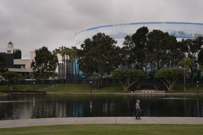 A man strolls past the Long Beach Convention Center, Thursday, April 22, 2021, in Long Beach, Calif., where migrant children found at the U.S.-Mexico border without a parent will be temporarily housed. The center is able to house up to 1,000 children and the first children are expected to arrive Thursday afternoon. (AP Photo/Jae C. Hong)