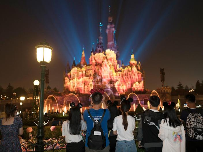 This image shows Disneyland and the night while people are looking at the lights behind the castle.