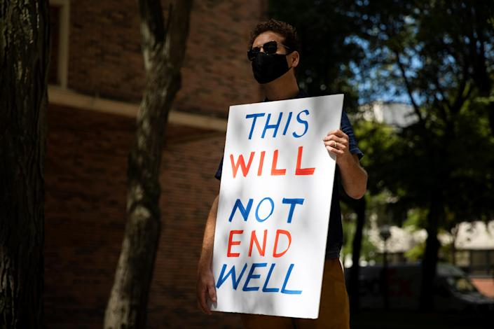 A faculty member holds a sign as students and teachers protest in-person classes at the University of Michigan campus in Ann Arbor, on Aug 19. (Emily Elconin/Reuters)