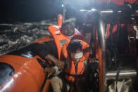 25-year-old Santa, originally from the Ivory Coast clutches her 5-year-old daughter Timi's arm to prevent her from falling into the water, after being rescued by the Spanish NGO Open Arms rescue vessel in the Mediterranean Sea, international waters, Saturday, Feb. 13, 2021. Various African migrants drifting in the Mediterranean Sea after fleeing Libya on unseaworthy boats have been rescued. In recent days, the Libyans had already thwarted eight rescue attempts by the Open Arms, a Spanish NGO vessel, harassing and threatening its crew in international waters. (AP Photo/Bruno Thevenin)