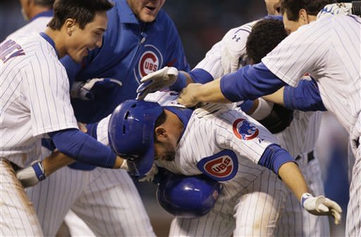 Chicago Cubs' David DeJesus, center, celebrates with teammates after he walked to first base during the 11th inning of a baseball game against the Los Angeles Dodgers in Chicago, Sunday, May 6, 2012. The Cubs won 4-3. (AP Photo/Nam Y. Huh)