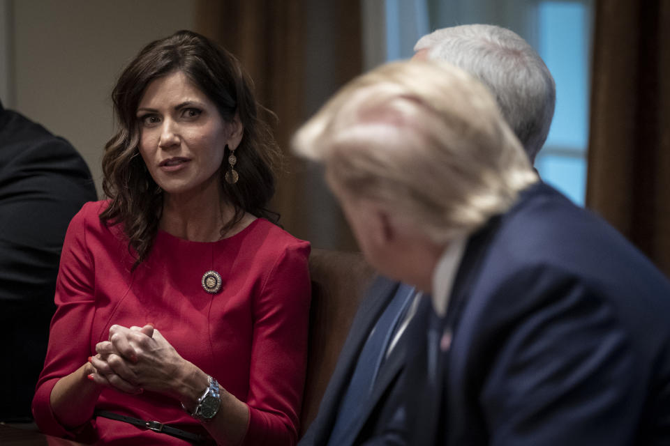 (L-R) Governor of South Dakota Kristi Noem speaks as U.S. President Donald Trump listens during a meeting about the Governors Initiative on Regulatory Innovation in the Cabinet Room of the White House on December 16, 2019 in Washington, DC. (Drew Angerer/Getty Images)
