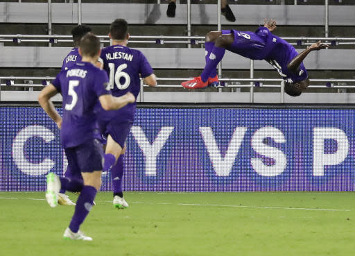 Orlando City's Benji Michel, right, does a back flip in front of teammates Dillon Powers (5) and Sacha Kljestan (16) after scoring a goal against the New England Revolution during the second half of a U.S. Open Cup soccer match, Wednesday, June 19, 2019, in Orlando, Fla. (AP Photo/John Raoux)