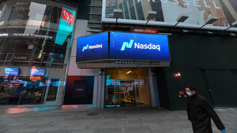 A man in a mask walks past the Nasdaq stock exchange in New York