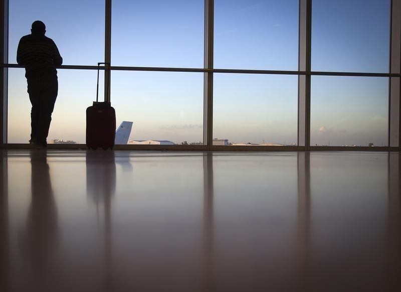 A passenger looks out the window at Miami International Airport in Miami