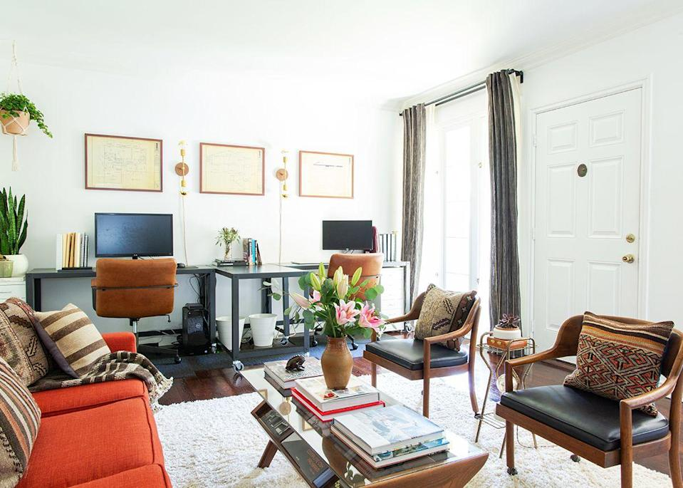 """Among her greatest finds were the vintage armchairs in the living room. """"I left the wood finish as-is and had the seat cushions rebuilt while preserving the original black leather upholstery,"""" she explains. """"The Sears house blueprints are also really fun, and I love that they're above the desks,"""" she adds. """"They're a great reminder to appreciate the technology we have today—hand-drawing plans to scale is excruciating."""""""