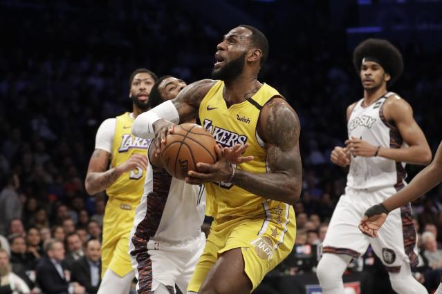 Los Angeles Lakers' LeBron James, center, drives past Brooklyn Nets' Kyrie Irving during the first half of an NBA basketball game Thursday, Jan. 23, 2020, in New York. (AP Photo/Frank Franklin II)