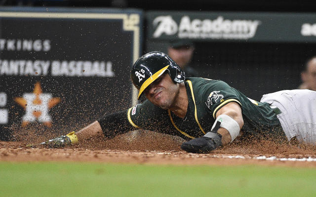 Oakland Athletics' Ramon Laureano slides safely into home to score on Robbie Grossman's RBI-double during the fourth inning of a baseball game against the Houston Astros, Sunday, April 7, 2019, in Houston. (AP Photo/Eric Christian Smith)