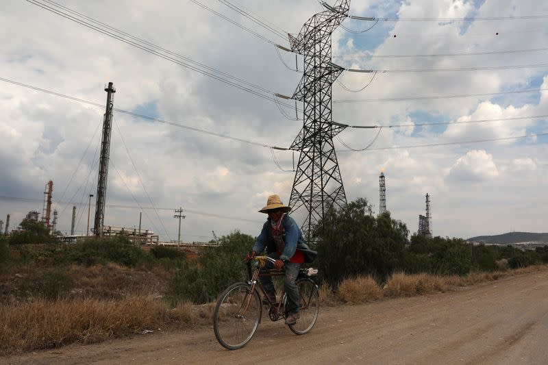 A man rides a bike on a road near high-voltage transmission lines near the Tula power plant owned by state-owned power company Commission Federal de Electricidad, or CFE, in Tula de Allende