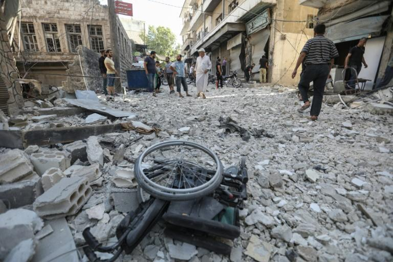 A wheelchair lies amid the rubble following an apparent Syria government air strike on the Idlib province town of Ariha on July 24, 2019