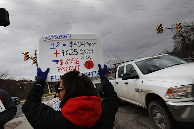 <p>West Virginia teachers, students and supporters hold signs on a Morgantown street as they continue their strike on March 2, 2018 in Morgantown, W.Va. (Photo: Spencer Platt/Getty Images) </p>