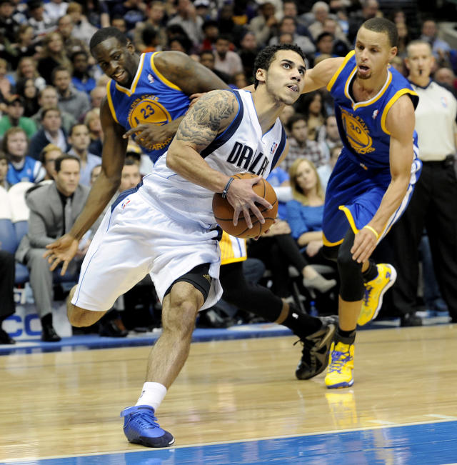 Dallas Mavericks point guard Shane Larkin drives past Golden State Warriors small forward Draymond Green (23) and point guard Stephen Curry (30) in the first half during an NBA basketball game on Wednesday, Nov. 27, 2013, in Dallas. (AP Photo/Matt Strasen)