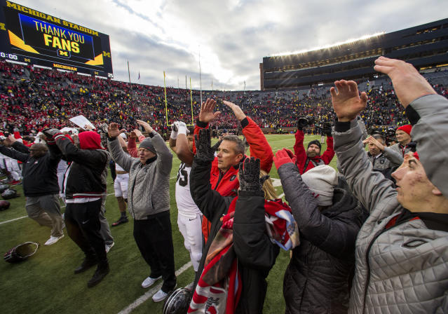 Ohio State head coach Urban Meyer (C) sings with his team and family members on the Michigan Stadium field on Saturday. (AP Photo/Tony Ding)