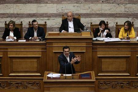 Greek PM Tsipras addresses lawmakers before a parliamentary vote on the latest round of austerity Greece has agreed with its lenders, in Athens