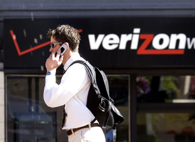FILE - A Monday, July 28, 2008 photo from files showing Eric Roden speaking on his cell phone as he walks past a Verizon store in Portland, Ore., Britain's Vodafone PLC, one of the world's largest mobile phone companies, confirmed Thursday that it was in discussions with Verizon Communications to sell its operations in the United States. The British wireless provider is mulling its options for its 45 percent stake in the U.S.'s Verizon Wireless, of which Verizon Communications owns the other 55 percent. Analysts have suggested that Verizon wants to pay around $100 billion for Vodafone's stake, although reports have said that U.K. group is pressing for as much as $130 billion.(AP Photo/Don Ryan, File)