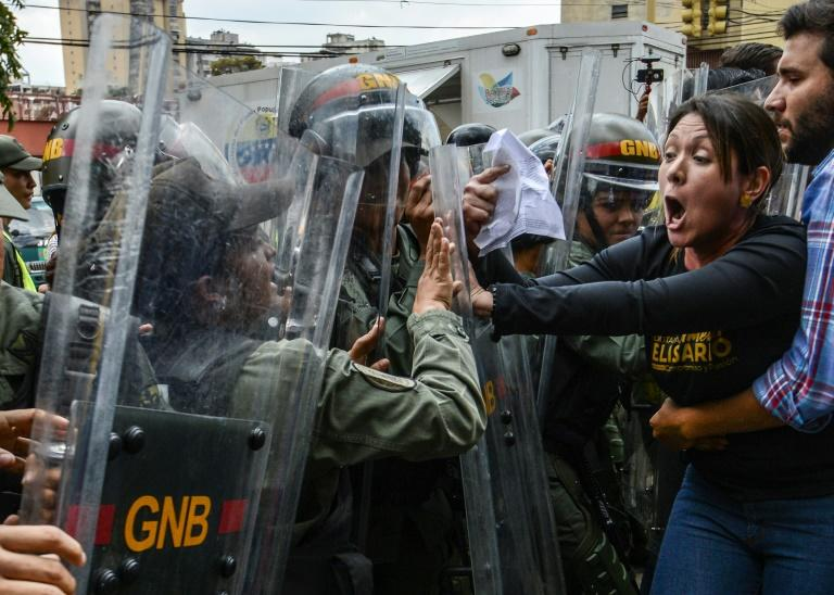 Venezuelan opposition deputy Amelia Belisario (2nd-R) scuffles with National Guard during a protest in front of the Supreme Court in Caracas