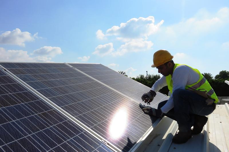 Construction worker installing solar panels on rooftop.