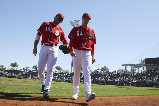 Cincinnati Reds first baseman Joey Votto (19) and Reds starting pitcher Sonny Gray (54) talk as they walk off the field together during the second inning of a spring training baseball game against the Seattle Mariners Wednesday, Feb. 26, 2020, in Goodyear, Ariz. (AP Photo/Ross D. Franklin)