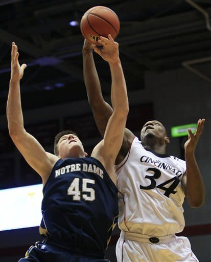 Cincinnati forward Yancy Gates (34) fights for a rebound with Notre Dame forward Jack Cooley in the first half of an NCAA college basketball game, Wednesday, Jan. 4, 2012, in Cincinnati. (AP Photo/Al Behrman)