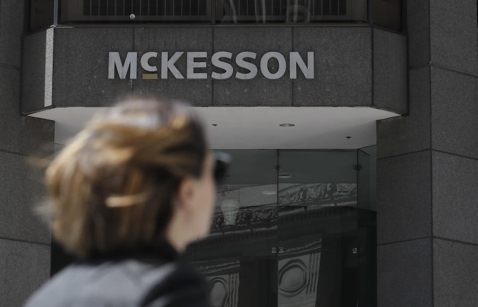 FILE - In this July 17, 2019 file photo, a pedestrian passes a McKesson sign on an office building in San Francisco. Four companies say they'll move ahead with a $26 billion settlement of lawsuits over the opioid crisis. An announcement from drug distributors AmerisourceBergen, Cardinal Health and McKesson came Saturday, Sept. 4, 2021. (AP Photo/Jeff Chiu, File)