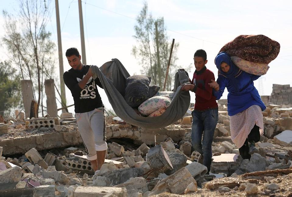 Syrians collect items from their destroyed house in the Al-Shallal suburb of the northeastern town of Al-Hol in Syria's Hasakeh province, on November 19, 2015, after Syrian Democratic Forces (SDF) re-took control of the area from Islamic State (IS) (AFP Photo/Delil Souleiman)