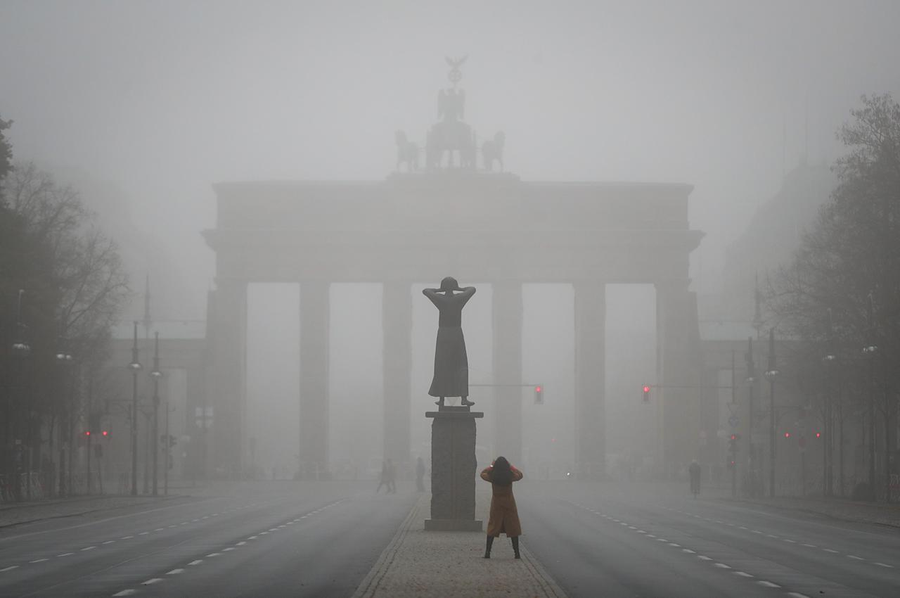 <p>A passerby takes photos of the Brandenburg Gate during mist in Berlin, Germany, Nov. 16, 2016. (Photo: KAY NIETFELD/EPA) </p>