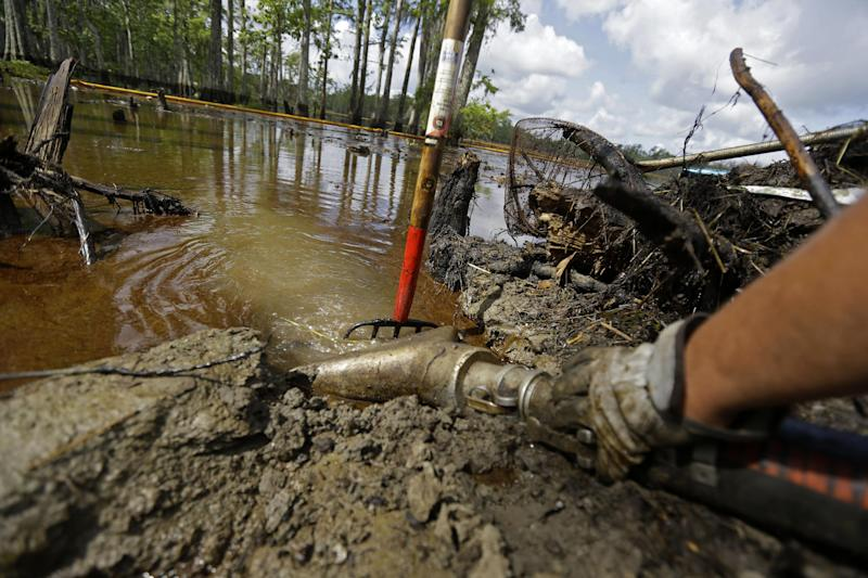 In this Thursday, June 27, 2013 photo, contractors use a vacuum truck to clean up crude oil that has risen to the surface of an approximate 22-acre sinkhole in Bayou Corne, La. Neighbors in tiny Bayou Corne face a wrenching decision after a huge sinkhole opened up near their community: Do they stay put or should they pack up and move? The sinkhole resulted from a collapsed underground salt dome cavern about 40 miles south of Baton Rouge. After oil and natural gas came oozing up and acres of swampland liquefied into muck, the community's 350 residents were advised to evacuate. Texas Brine Co., the operator of the salt dome, is negotiating buyouts of residents who have not joined lawsuits against the company. (AP Photo/Gerald Herbert)