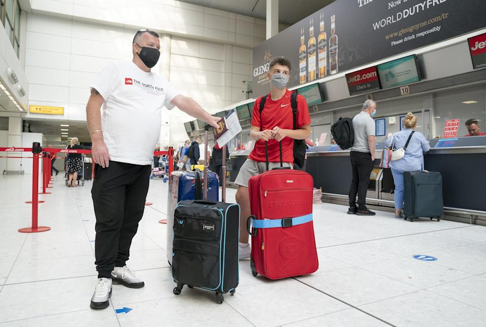 Brian Smith and his son Dillon wait at the Jet2 check-in desk (Jane Barlow/PA) (PA Wire)