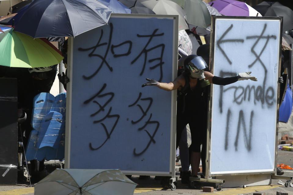 A protestor gestures from behind barricades during a confrontation with police at the Hong Kong Polytechnic University in Hong Kong, Sunday, Nov. 17, 2019. (AP Photo/Achmad Ibrahim)