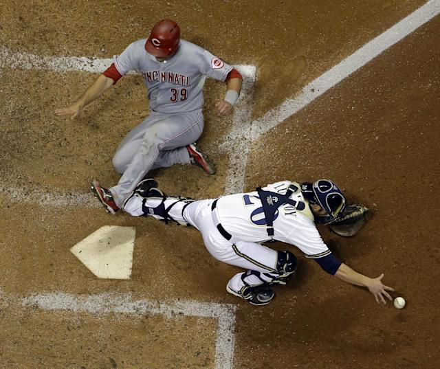 Cincinnati Reds' Devin Mesoraco (39) slides safely home as Milwaukee Brewers catcher Jonathan Lucroy has trouble with the throw during the fifth inning of a baseball game Thursday, Aug. 15, 2013, in Milwaukee. Mesoraco scored from second on a hit by Zack Cozart. (AP Photo/Morry Gash)