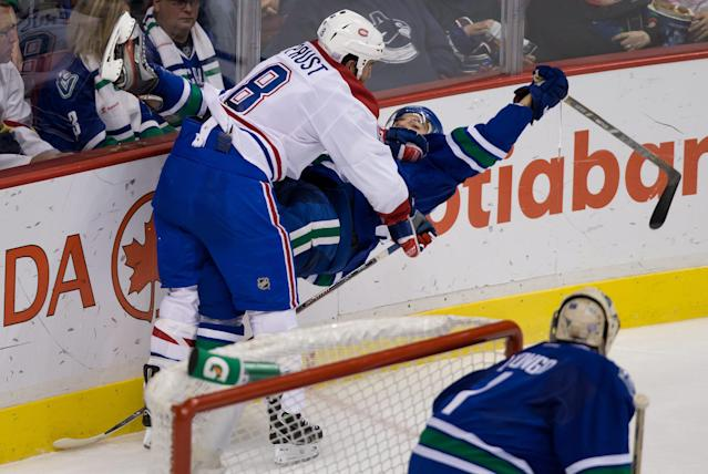 Montreal Canadiens' Brandon Prust, left, checks Vancouver Canucks' Chris Tanev behind Canucks' goalie Roberto Luongo during the second period of an NHL hockey game in Vancouver, British Columbia, Saturday, Oct. 12, 2013. (AP Photo/The Canadian Press, Darryl Dyck)