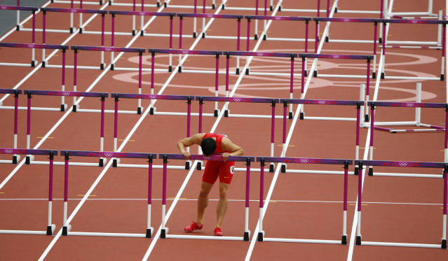 China's Liu Xiang kisses the last hurdle in his lane after his men's 110m hurdles round 1 heat at the London 2012 Olympic Games at the Olympic Stadium August 7, 2012. Liu crashed out of the heats in the 110 metres hurdles at the London Olympics on Tuesday in an echo of his injury-induced withdrawal from the same stage of the Beijing Games four years ago. REUTERS/David Gray (BRITAIN - Tags: OLYMPICS SPORT ATHLETICS TPX IMAGES OF THE DAY)