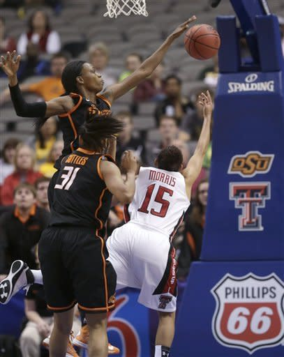 Texas Tech guard Casey Morris (15) has her shot blocked by Oklahoma State forward Toni Young (15) as Kendra Suttles (31) watches during the first half of an NCAA college basketball game in the Big 12 women's tournament Saturday, March 9, 2013, in Dallas. Oklahoma State won 59-54. (AP Photo/LM Otero)