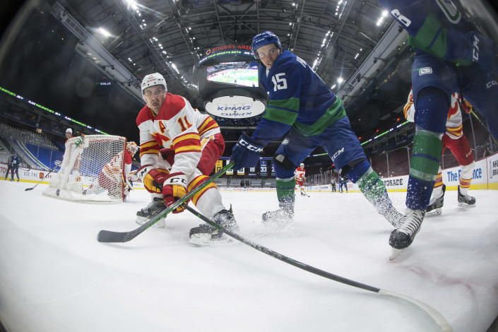 Calgary Flames' Mikael Backlund (11), of Sweden, and Vancouver Canucks' Matthew Highmore (15) vie for the puck during the first period of an NHL hockey game, Sunday, May 16, 2021, in Vancouver, British Columbia. (Darryl Dyck/The Canadian Press via AP)