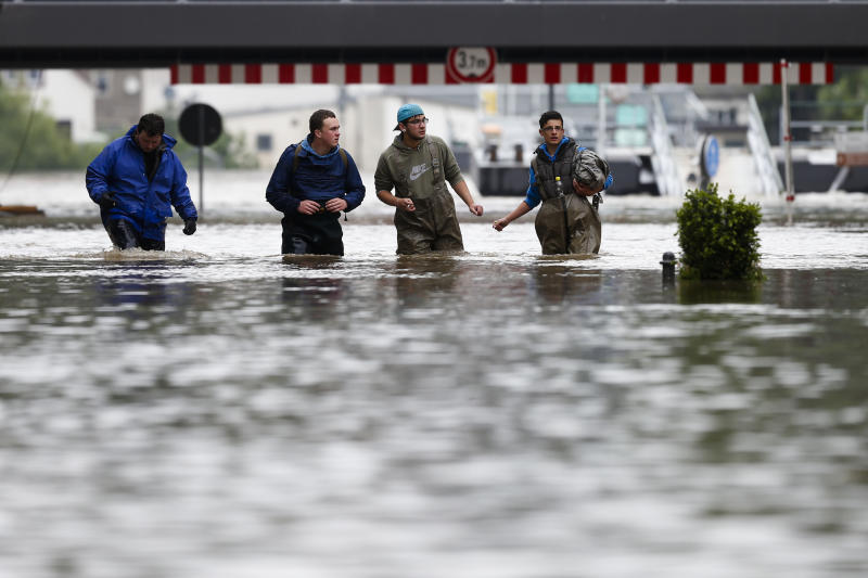 Volunteers walk through the flooded streets of the city Pirna, Germany, Tuesday, June 4, 2013.   After heavy rainfalls swollen rivers flooded areas in Germany, Austria , Switzerland and Czech Republic. (AP Photo/Markus Schreiber)