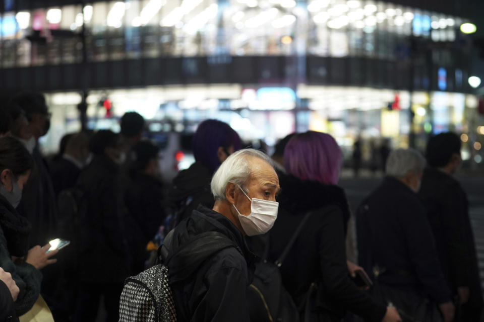 A man wearing a protective mask to help curb the spread of the coronavirus waits at a pedestrian crosswalk Wednesday, Nov. 25, 2020, in Tokyo. The Japanese capital confirmed more than 400 new coronavirus cases on Wednesday. (AP Photo/Eugene Hoshiko)