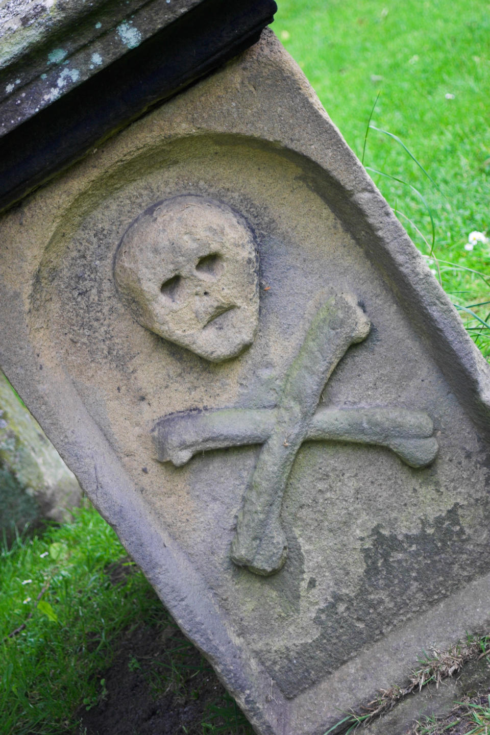 Tomb with skull and cross bones on it in the graveyard of Saint Lawrence's Church Eyam, Derbyshire. (Photo by: MyLoupe/Universal Images Group via Getty Images)