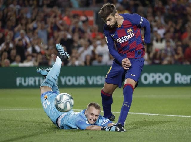 Barcelona's Gerard Pique, right, scores his side's third goal past Valencia's goalkeeper Jasper Cillessen during the Spanish La Liga soccer match between FC Barcelona and Valencia CF at the Camp Nou stadium in Barcelona, Spain, Saturday, Sep. 14, 2019. (AP Photo/Joan Monfort)