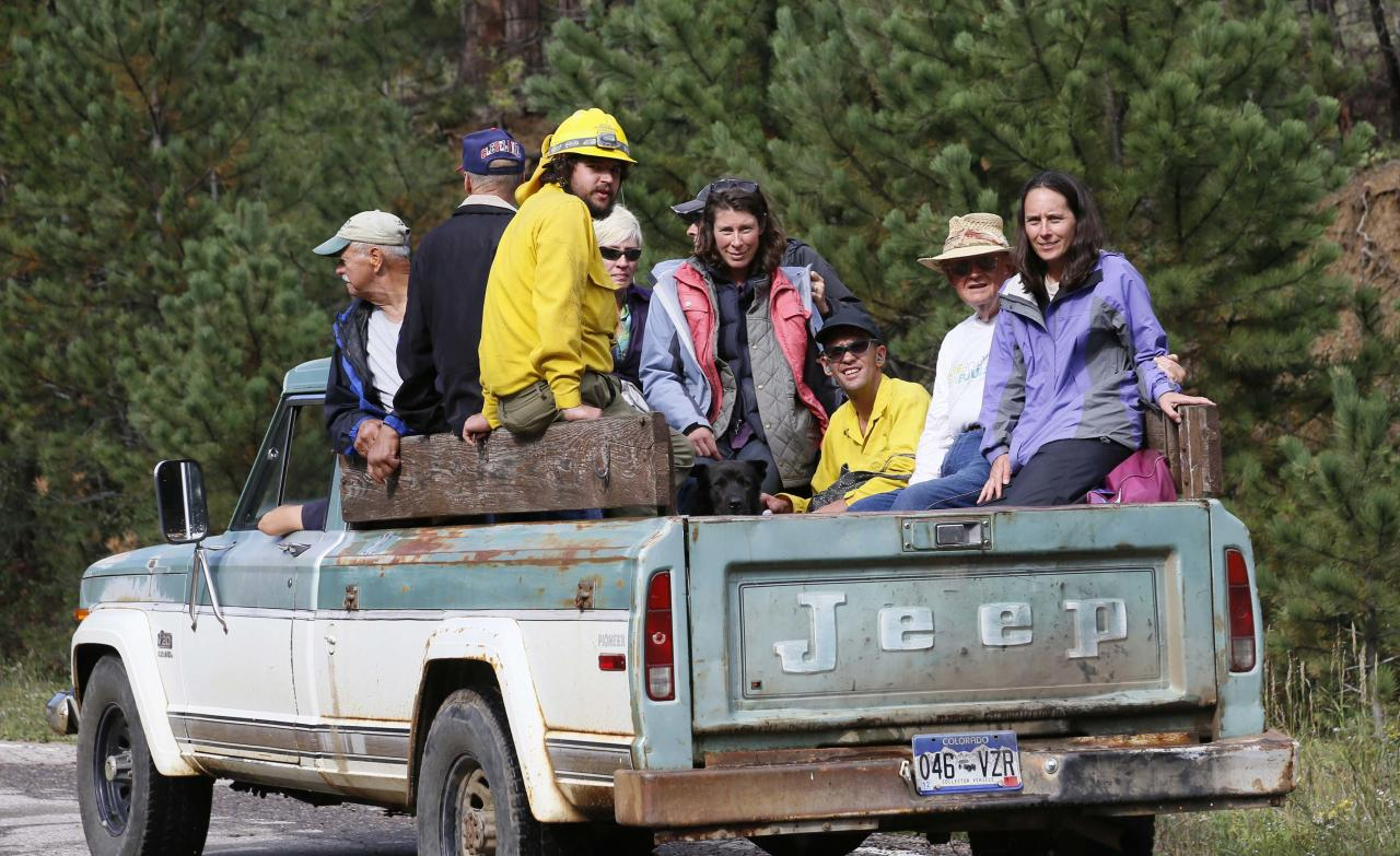 Residents are transported in a pickup truck to be evacuated by helicopter from Jamestown, Colorado, after a flash flood destroyed much of the town, September 14, 2013. Colorado farming communities along the South Platte River were ordered to evacuate ahead of a predicted surge in the flooding, which may have claimed a fifth life and has left many still unaccounted for, authorities said on Saturday. REUTERS/Rick Wilking (UNITED STATES - Tags: DISASTER ENVIRONMENT TPX IMAGES OF THE DAY)