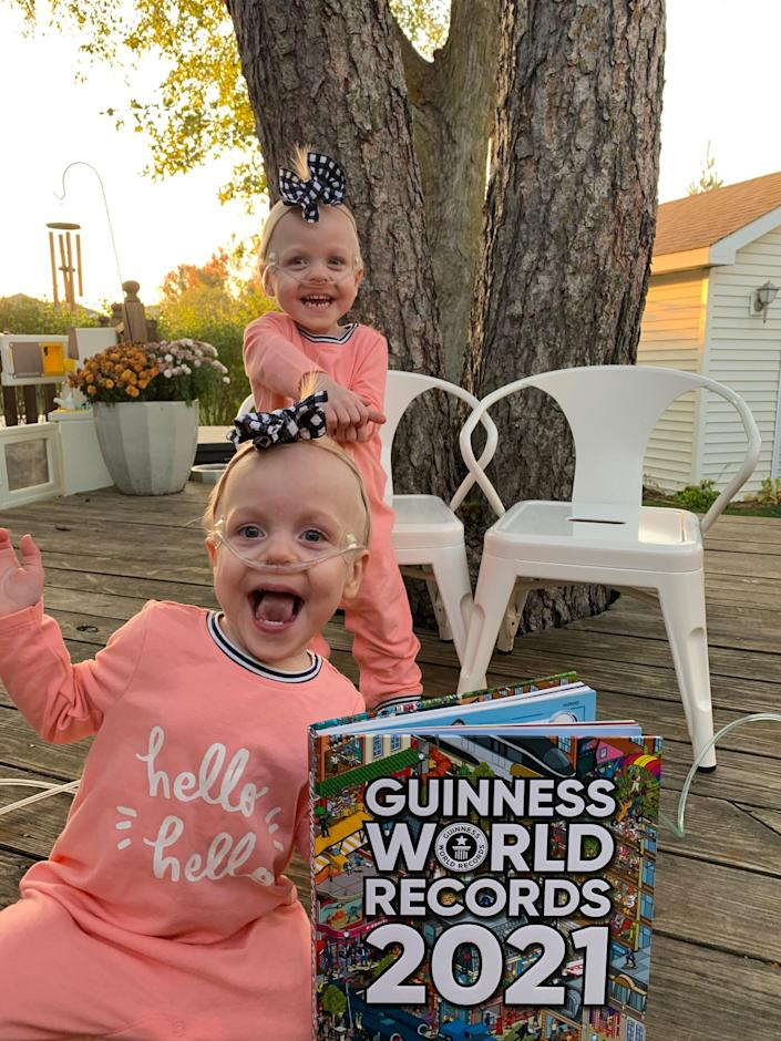 Identical twin sisters Keeley, back, and Kambry Ewoldt of Dysart pose with their copy of the Guinness World Records. The girls are in the book as the world's most premature twins, born almost four months early.
