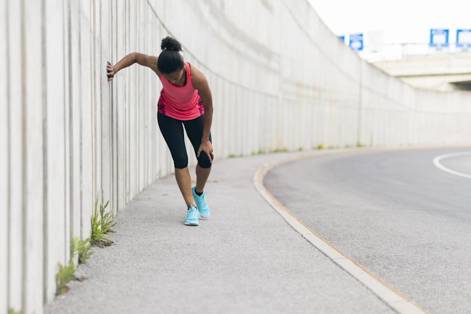 Young woman taking a break from running, having a knee injury
